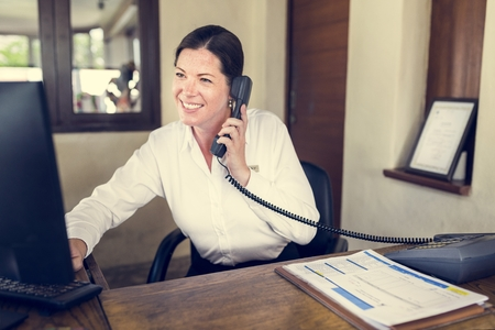 Female resort receptionist working at the front desk Stock Photo