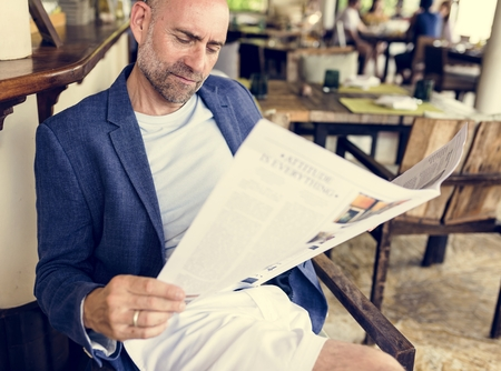 Casual man reading a newspaper at a restaurant