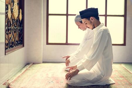 Muslim men praying in Tashahhud posture Stock Photo - 110548287