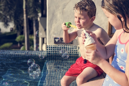 Kids blowing bubbles by swimming pool