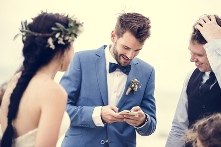 Groom occupied with phone at beach wedding ceremony Stock Photo
