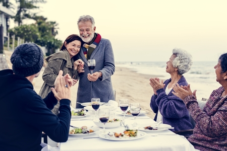 Mature friends having a dinner party at the beach Stock Photo