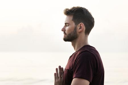 Man practicing yoga on the beach Stock Photo