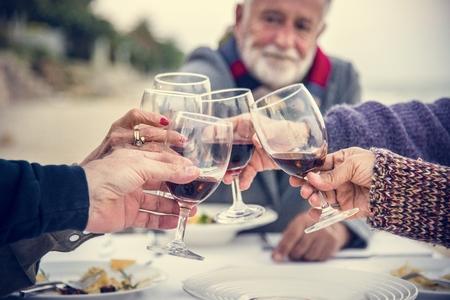 Personas mayores brindando con vino tinto en la playa.