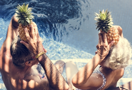 Couple holding pineapples above their heads Фото со стока