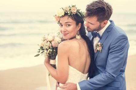 Junges Paar, das am Strand heiratet