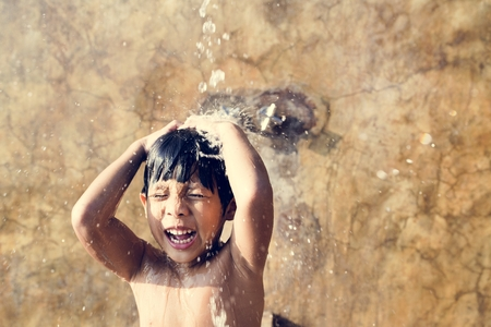 Little boy taking a shower by a swimming pool