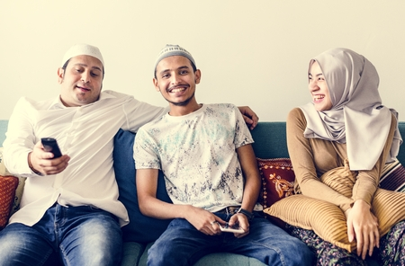 Muslim family watching tv at home