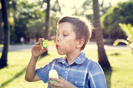 Boy blowing soap bubbles in the park Stock Photo
