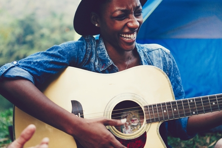 African American woman playing a guitar at a campsite Standard-Bild