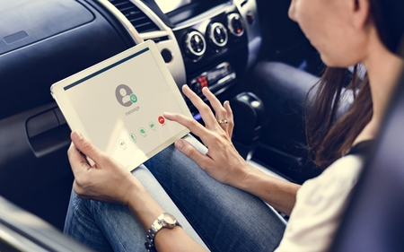 Vrouw met behulp van een digitale tablet in de auto