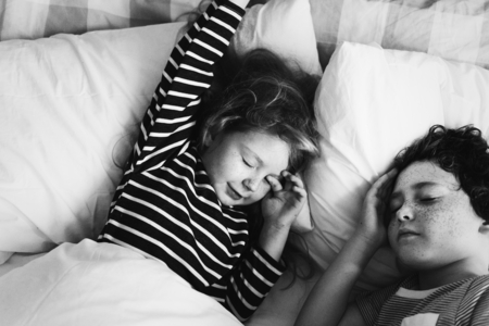 Caucasian siblings sleeping in the bed