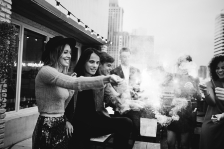 Friends playing with sparklers at outdoor party