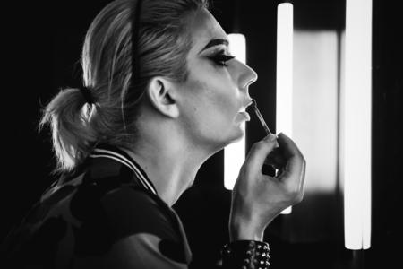 Drag queen brengt lippenstift op haar lippen Stockfoto