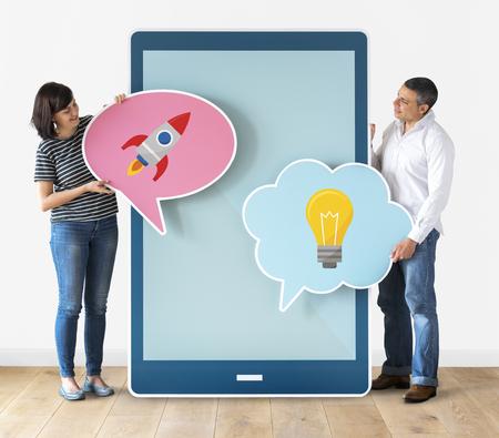 Couple holding speech bubbles and tablet Foto de archivo