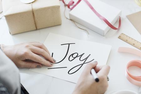 Woman writing a text Joy on a card