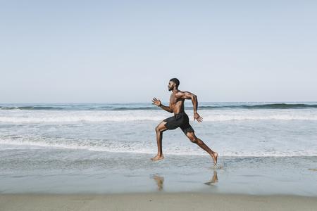 Uomo in forma che corre in spiaggia