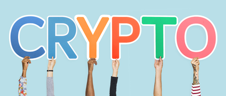 Hands holding up colorful letters forming the word crypto