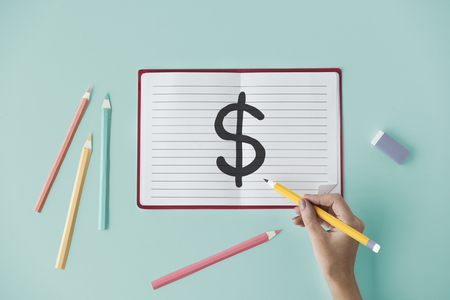 Hand drawing a dollar sign on a notebook