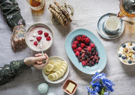 Woman enjoying berries and yogurt for breakfast
