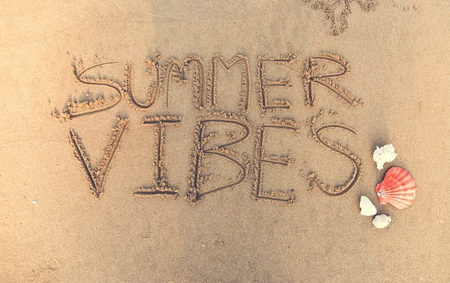 Summer vibes written in the sand