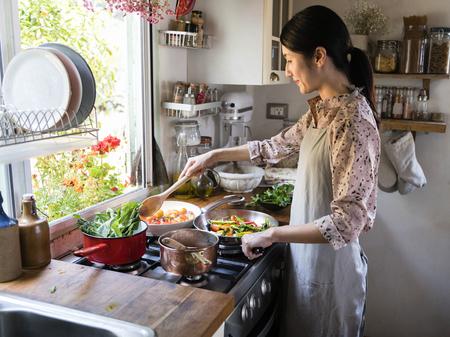 Frau kocht Mittagessen in einer Küche Standard-Bild