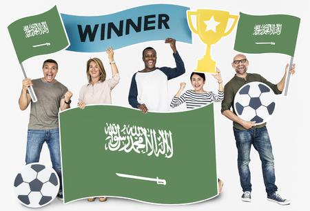 Diverse football fans holding the flag of Saudi Arabia Stock Photo