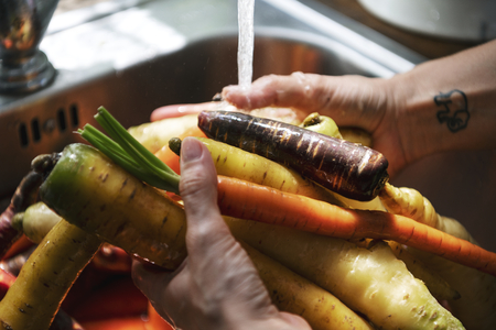 Chef cleaning carrots and turnips in the sink