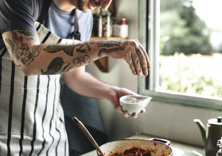 Tattooed man cooking in a countryside kitchen