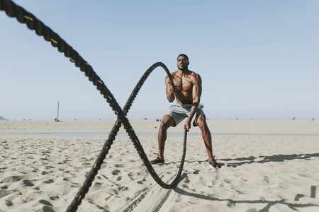 Fit man working out with battle ropes 写真素材