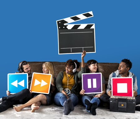 People holding media player icons and a clapper icon Stock Photo