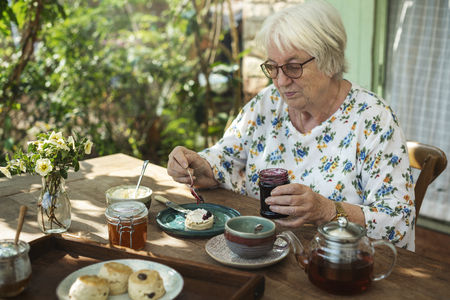 Senior woman having scones for breakfast
