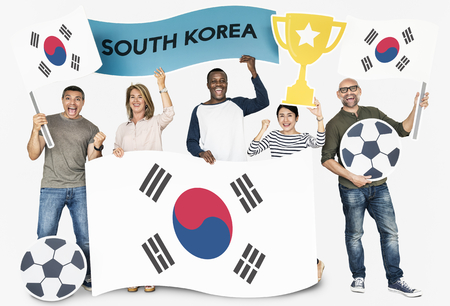 Diverse football fans holding the flag of Korea