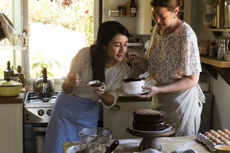 Donne che cuociono una torta al cioccolato in cucina