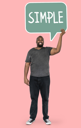 Cheerful man showing word simple in a speech bubble