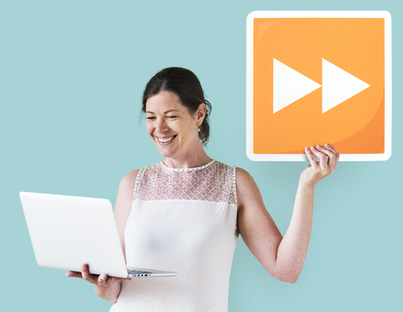 Woman holding a fast forward button and a laptop
