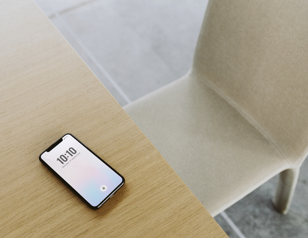 Mobile phone showing date and time on a wooden table Stock Photo