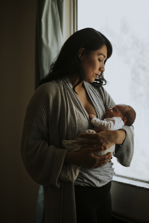 Mother holding her baby indoors Stock Photo