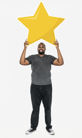 Cheerful man holding a golden star rating symbol