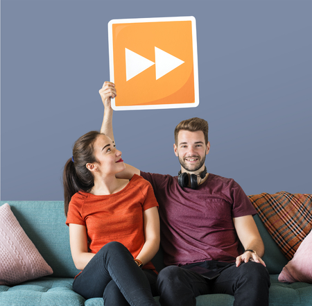 Young couple holding a fast forward button icon Stock Photo - 110600071