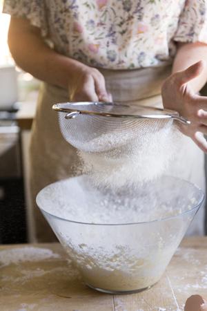 Woman sieving flour into a bowl