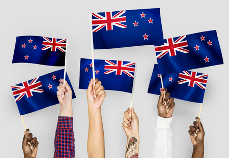 Hands waving flags of New Zealand