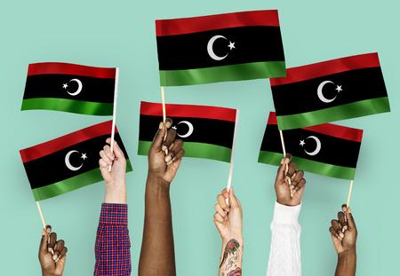 Mani che sventolano bandiere della Libia