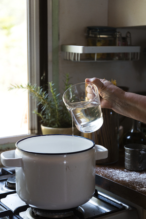 Cook pouring water into a pot Stock Photo