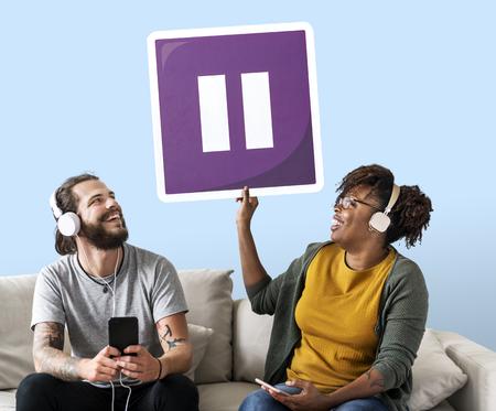 Pareja interracial escuchando música y sosteniendo un botón de pausa