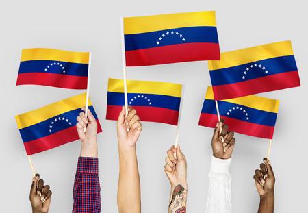 Hands waving flags of Venezuela 스톡 콘텐츠 - 110602898