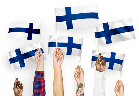 Hands waving flags of Finland