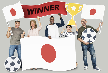 Diverse football fans holding the flag of Japan