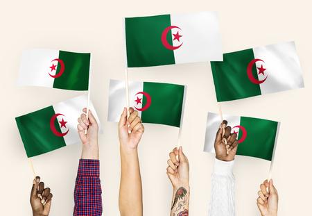 Hands waving flags of Algeria