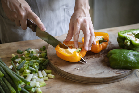 Cook slicing bell peppers on a cutting board Stockfoto